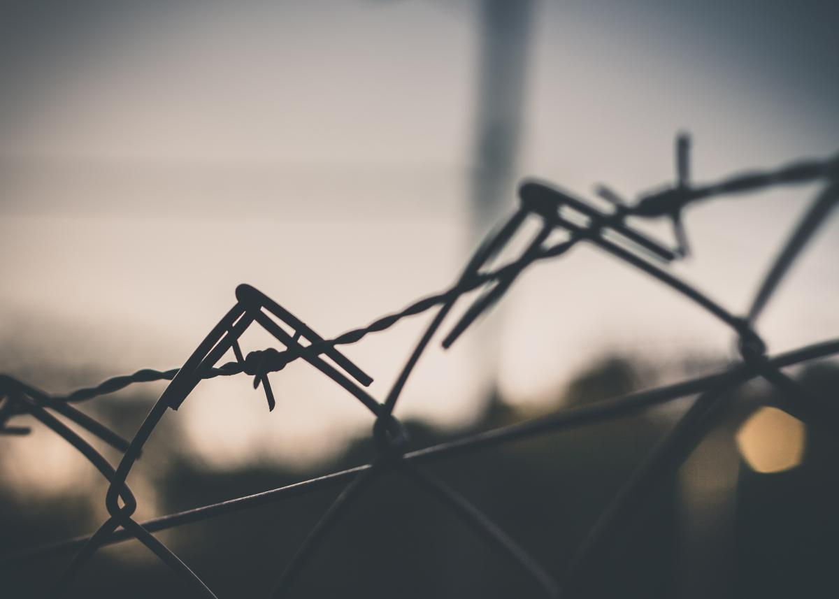 Колючая проволка на заборе  № 1701942 загрузить