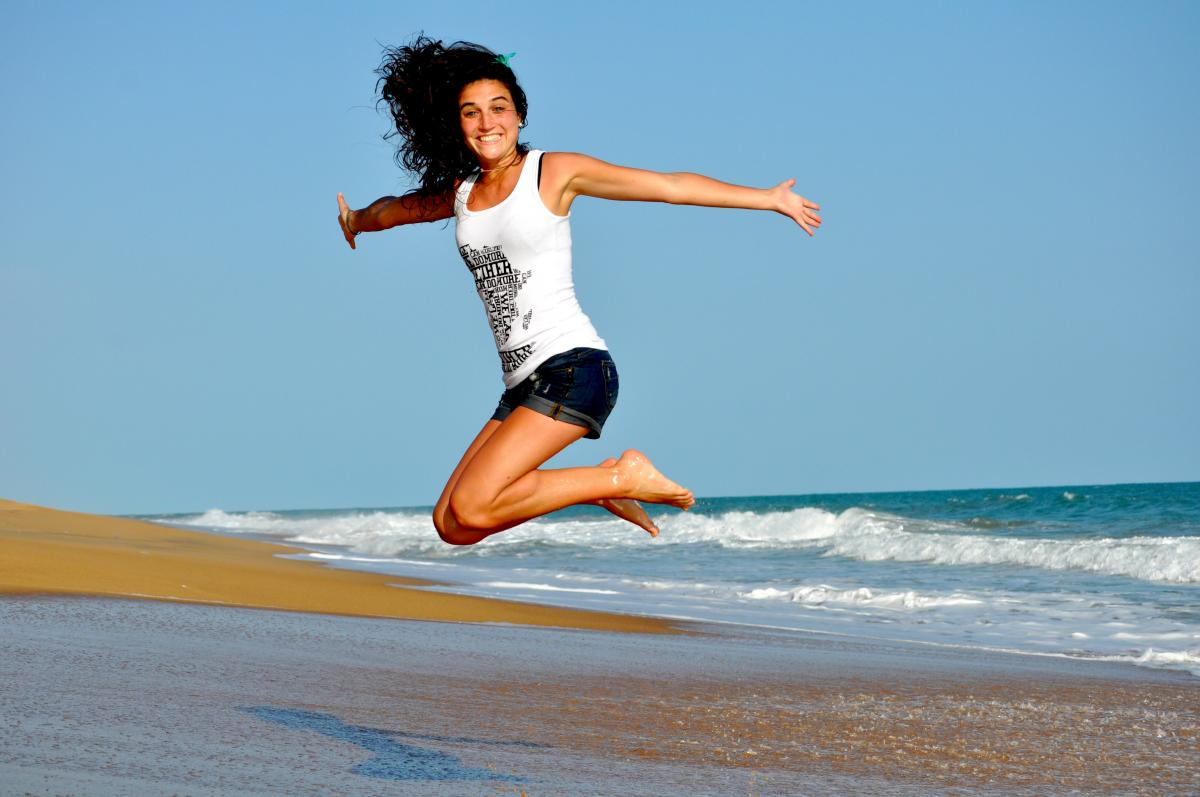 Woman in White Tanktop Jump over Beach Sand #33275
