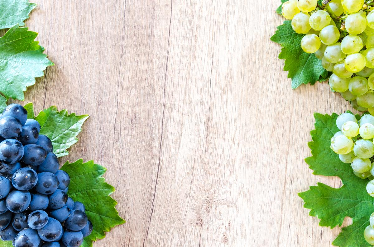 Blue Berries and Green Grapes on Beige Wooden Surface