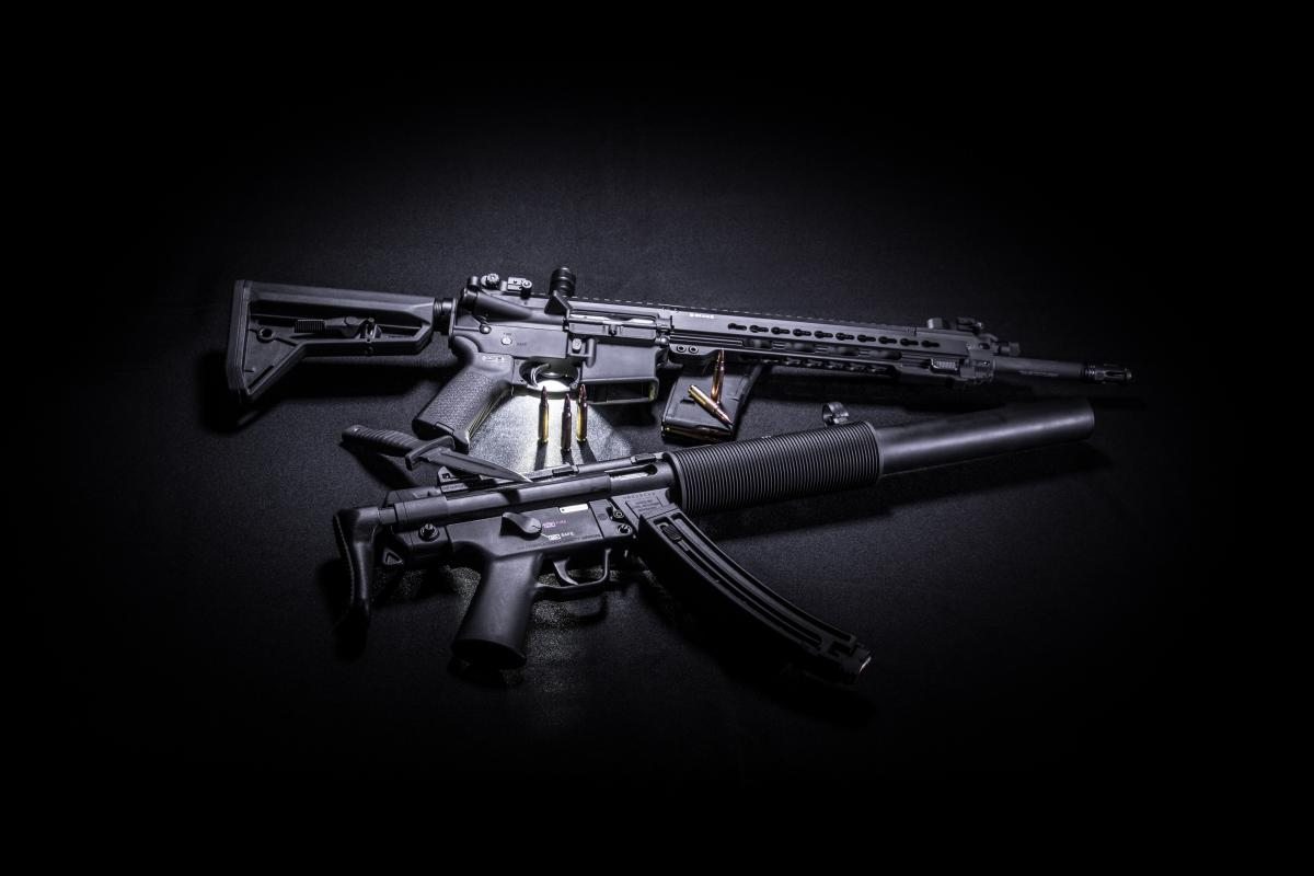 Photo of Two Black Assault Rifles, Knife, and bullets