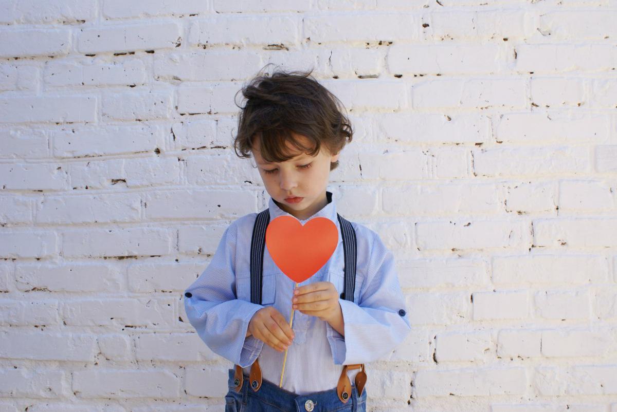 Photo of Boy Holding Heart-shape Paper on Stick