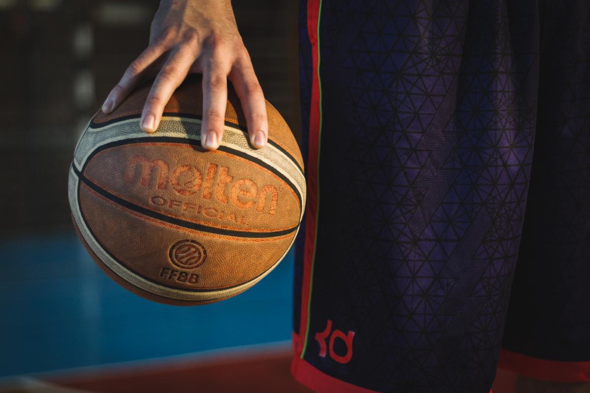 Hombre en azul y rojo pantalones cortos de pie sosteniendo Malten Baloncesto #34799