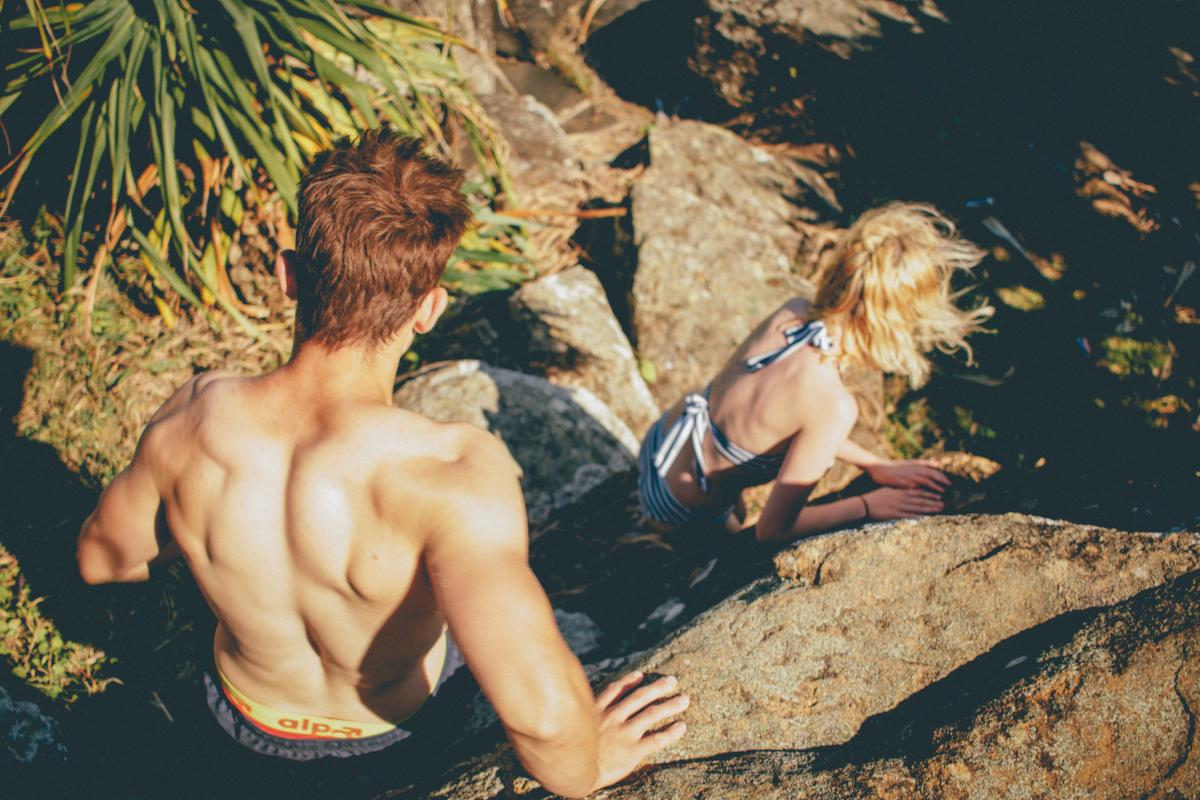 Topless Man Behind Woman Walking on Gray Rock Formation during Daytime #36653