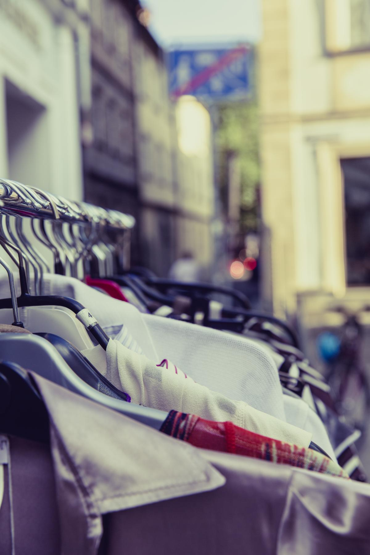 Shallow Focus Photography of Shirts Hang on Silver Clothes Rack Under Sunny Sky #37335