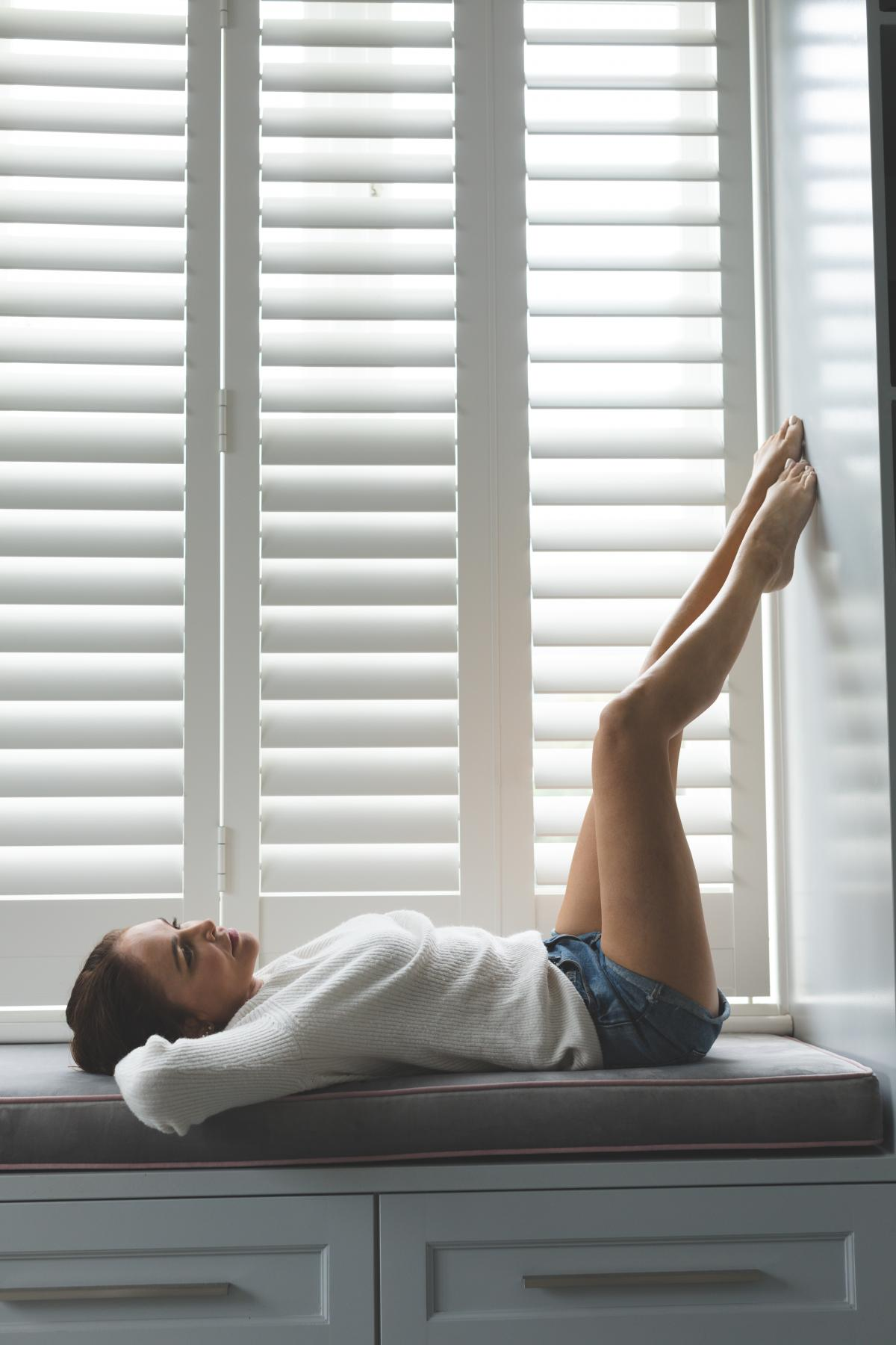 Woman relaxing on window seat in living room at comfortable home #410101