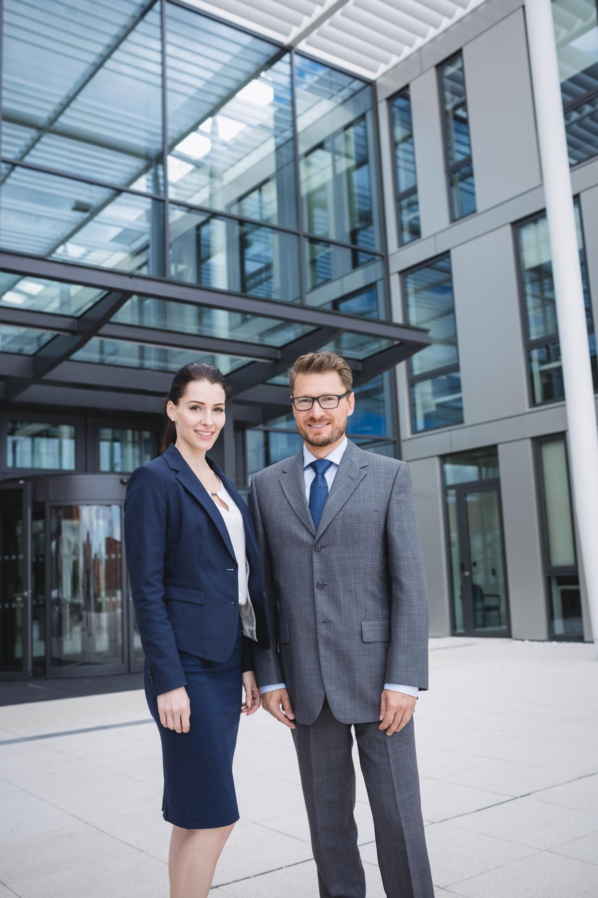 Confident businessman with colleague standing outside office building