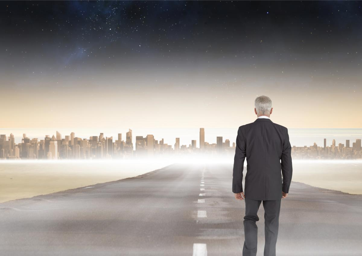 Businessman walking on road to city