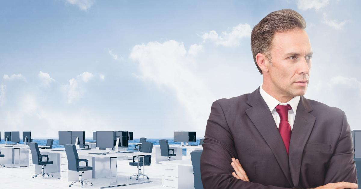 Businessman with arms crossed against office background