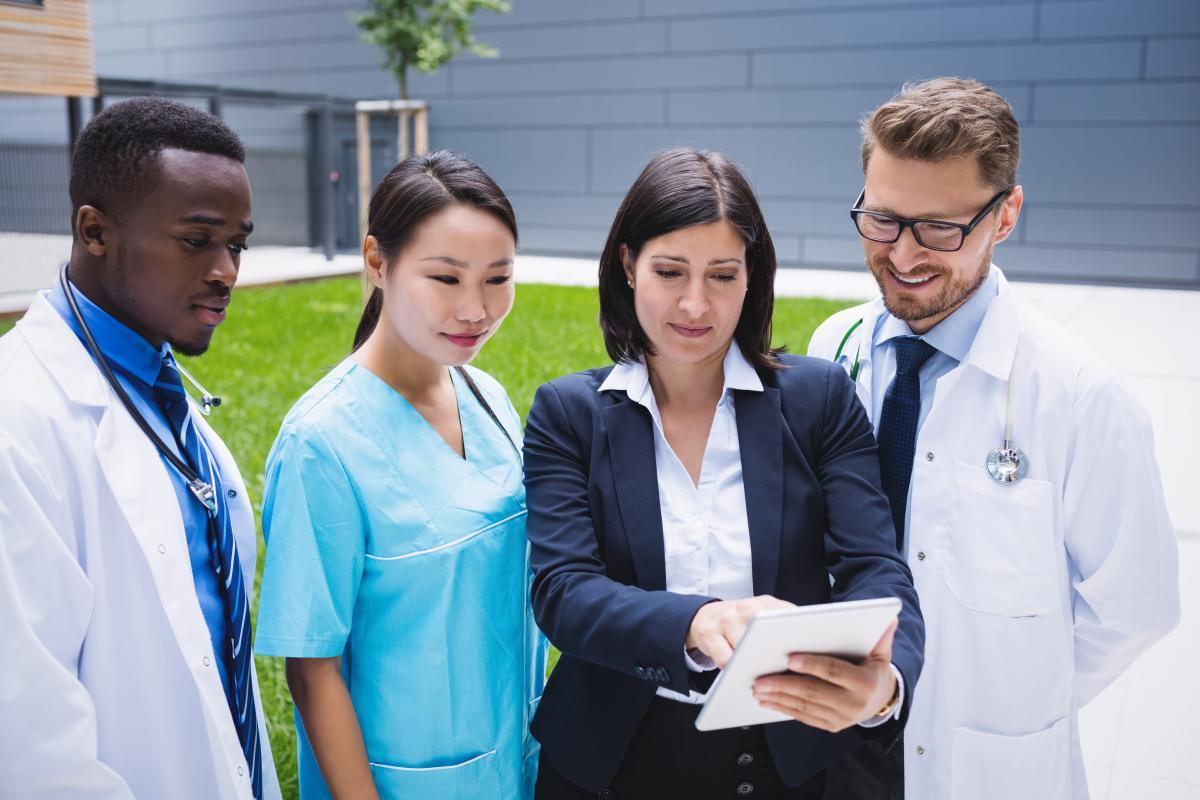 Team of doctors discussing over digital tablet
