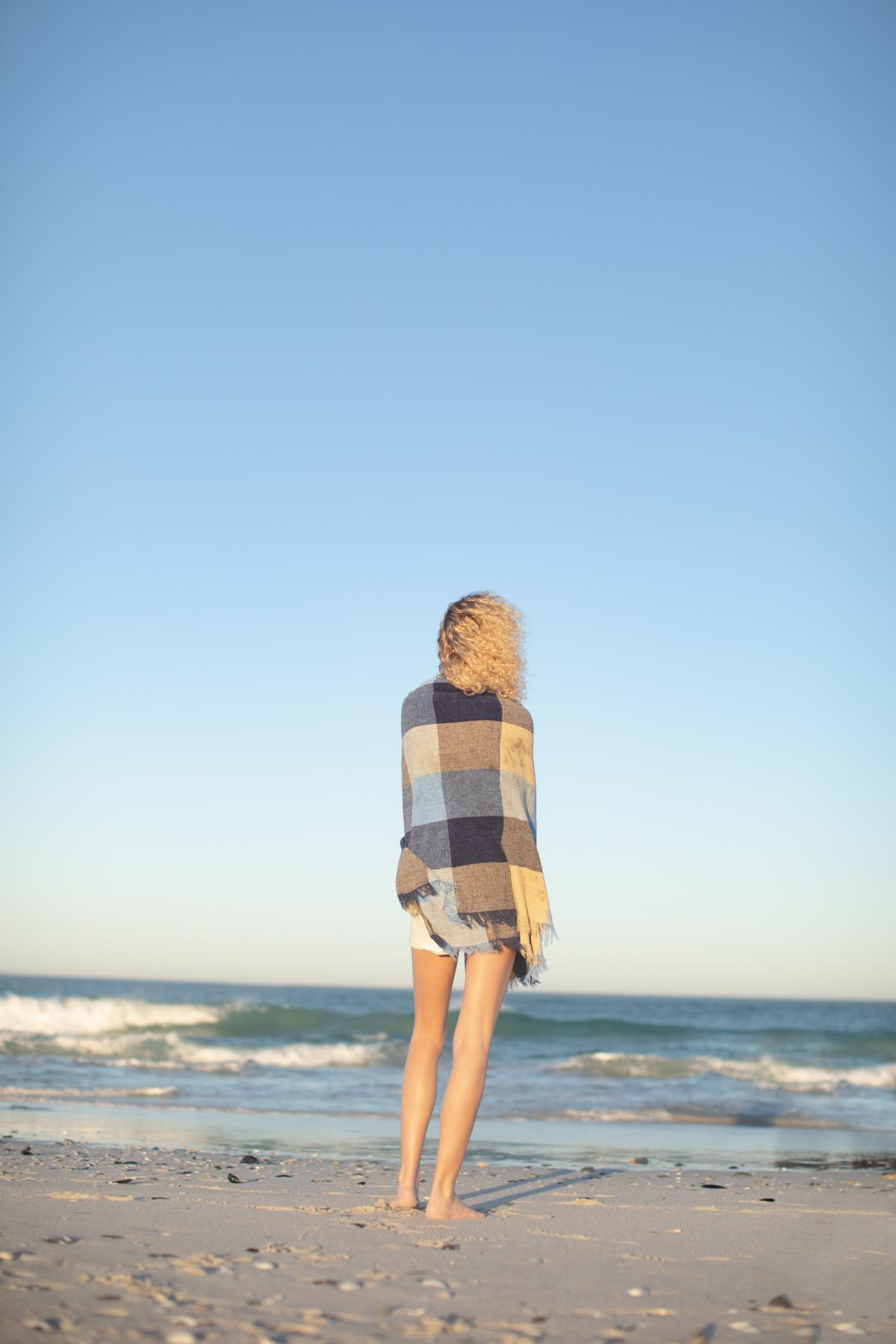 Woman wrapped in blanket standing on the beach #412161