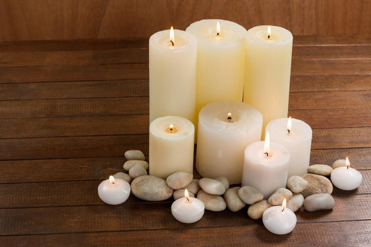 Close- up of white candles and pebbles stone on wood