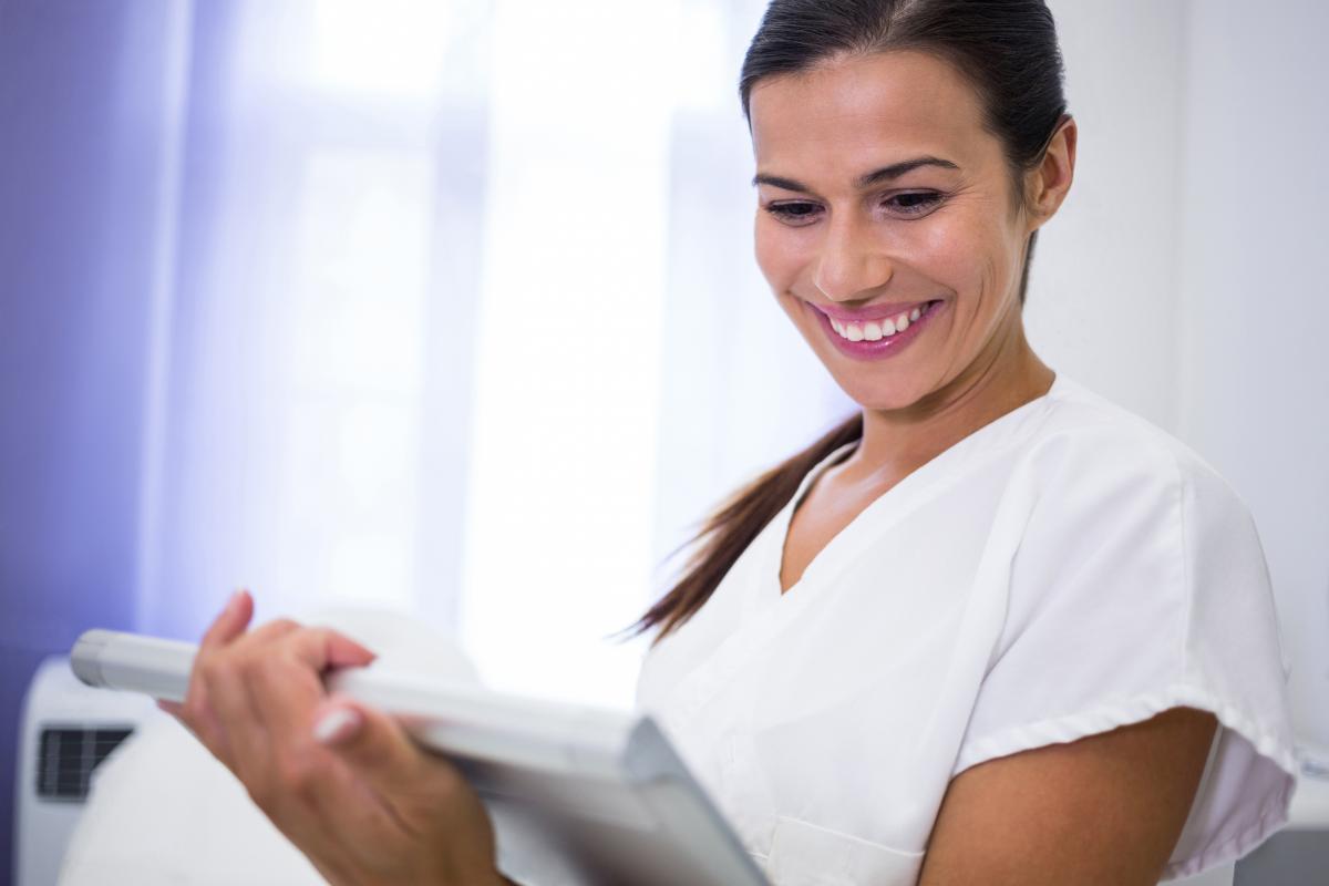 Smiling dentist using digital tablet