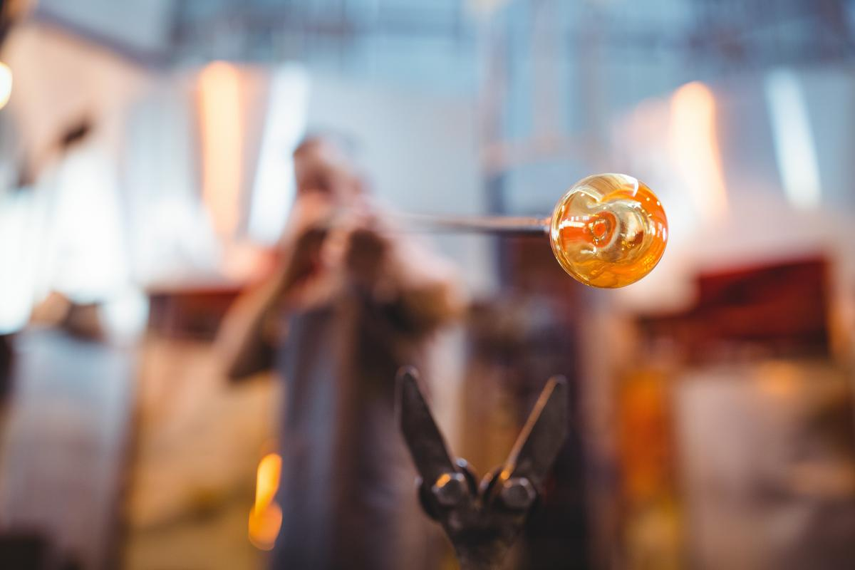 Glassblower shaping a glass on the blowpipe #414248