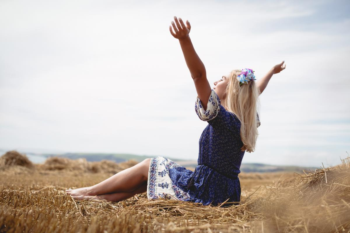 Blonde woman sitting in field with her arms raised #414271