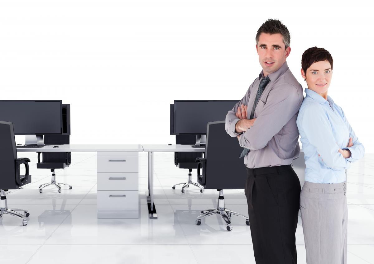 Male and female executive standing back to back with arms crossed in office
