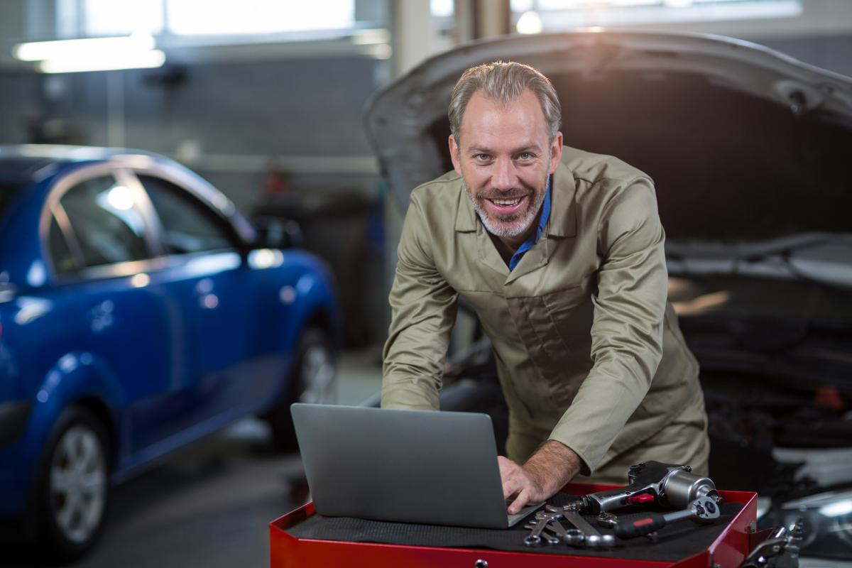 Portrait of mechanic using laptop #414482