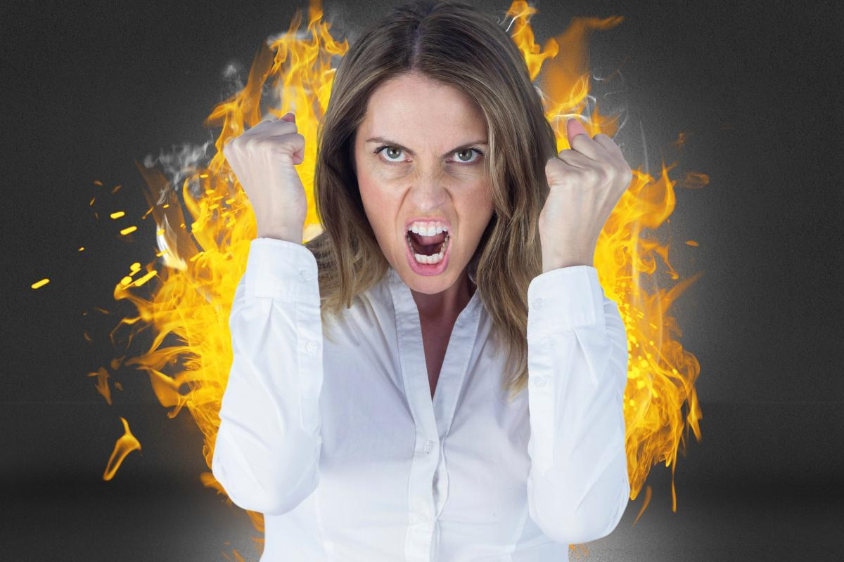 Digital composite image of angry businesswoman clenching fists against fire #414521
