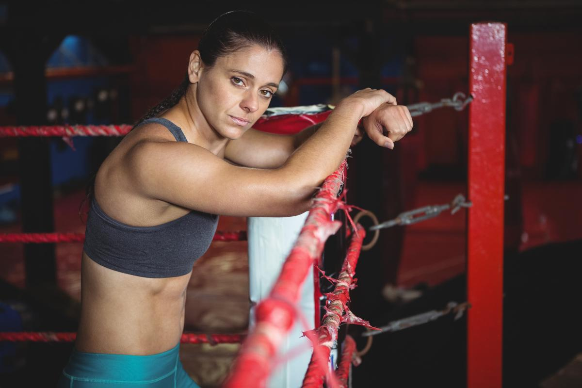 Confident female boxer leaning on boxing ring #416947