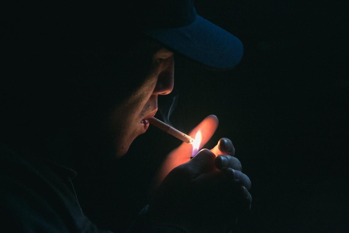 Man in Black Cap Lighting Cigarette during Nighttime