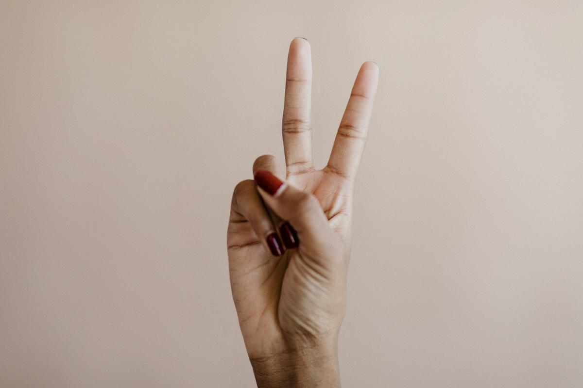 Woman showing a peace hand sign #417952