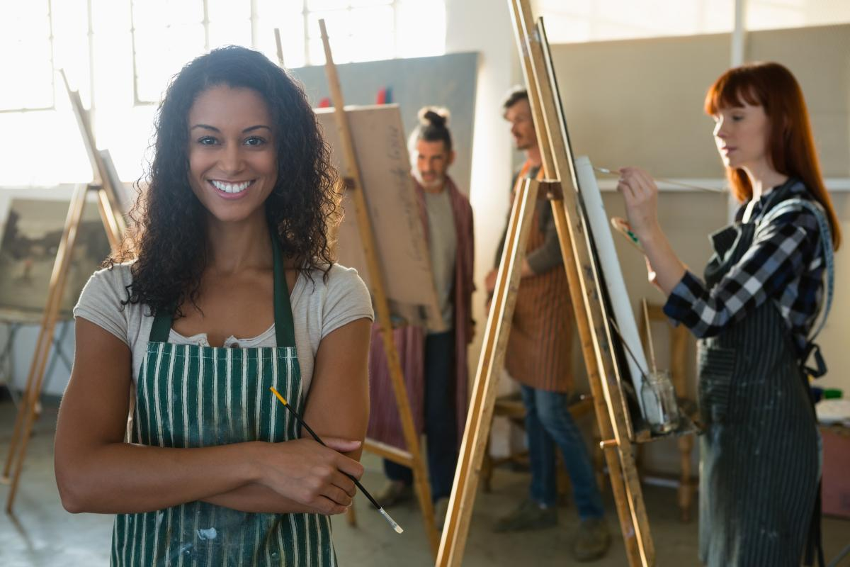 Portrait of smiling female artist with friends painting in background