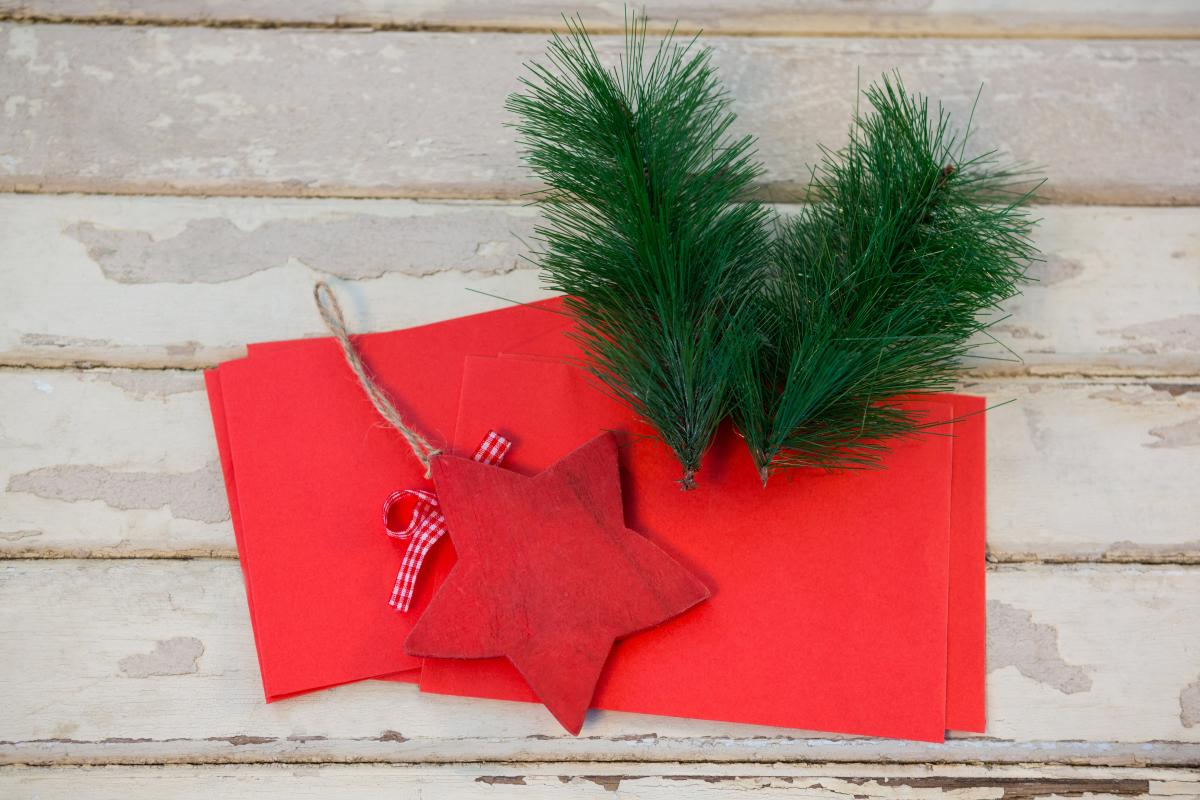Red envelopes, christmas fir and star on wooden plank