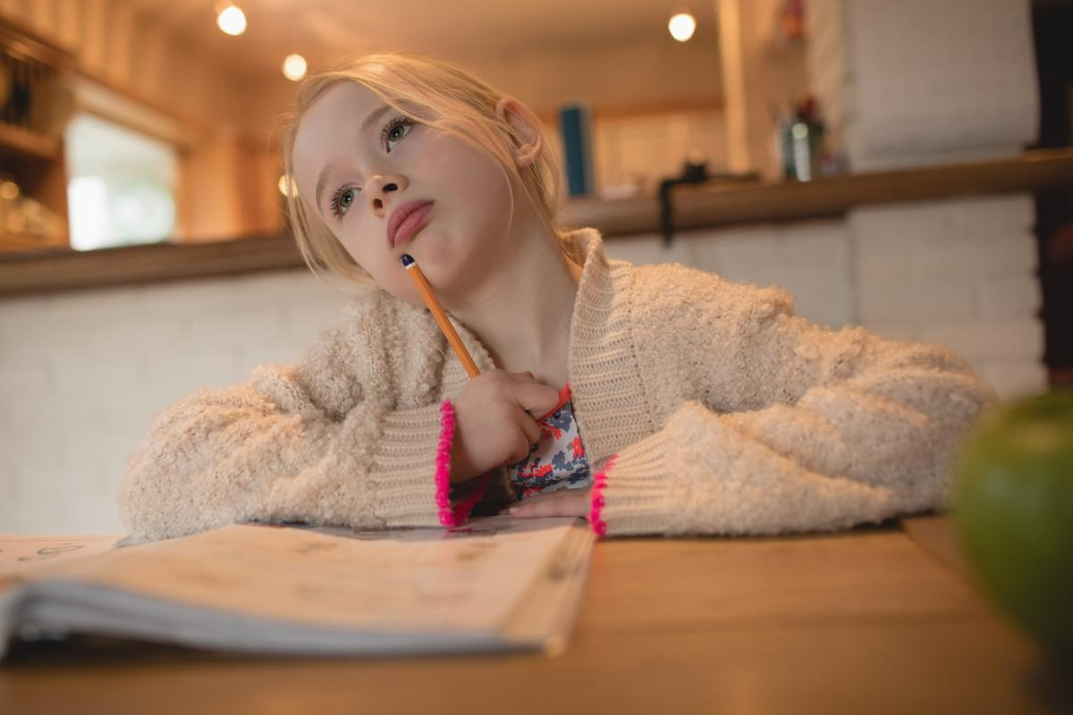 Thoughtful girl sitting at table and studying