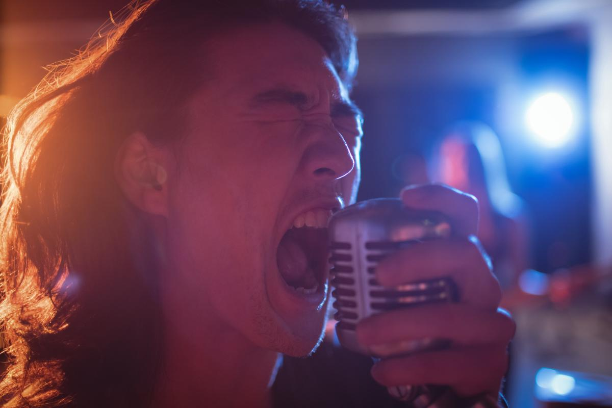 Close-up of male singer singing in studio