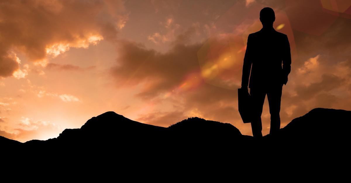 Silhouette businessman standing on mountain during sunset #419018