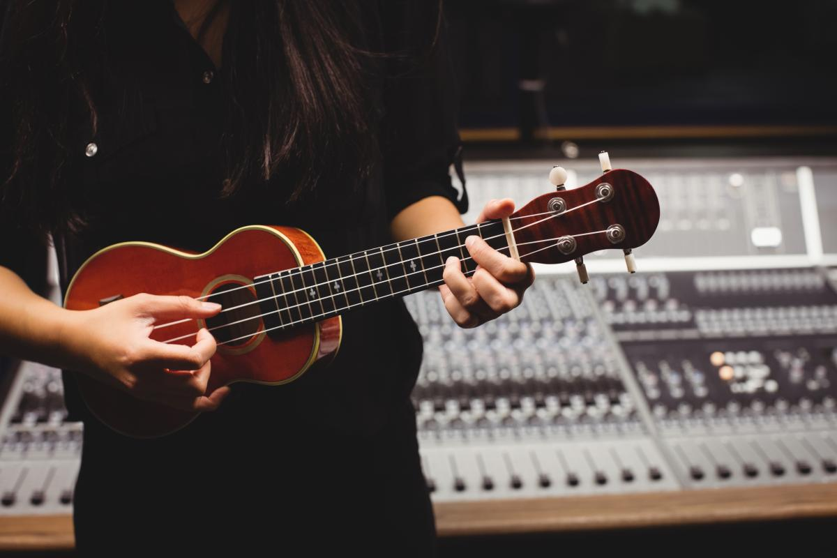 Mid-section female student playing guitar
