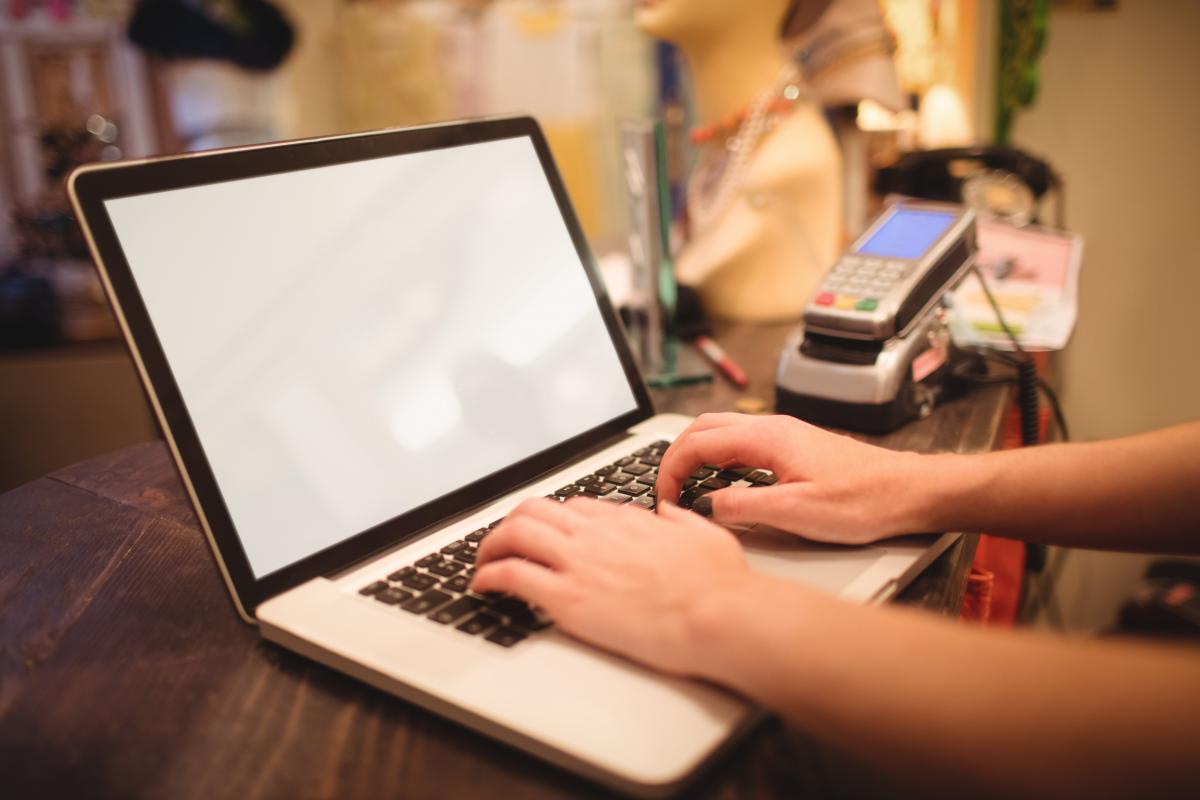 Hands of female staff using laptop at a counter #419384