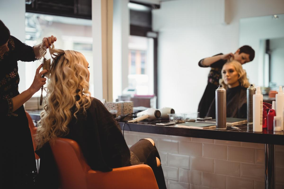 Female hairdresser styling clients hair #419387