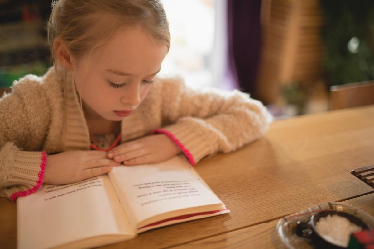Cute girl sitting at table and reading book