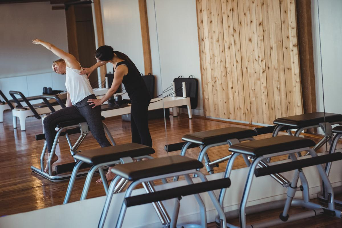 Trainer helping a woman while practicing pilates #420880