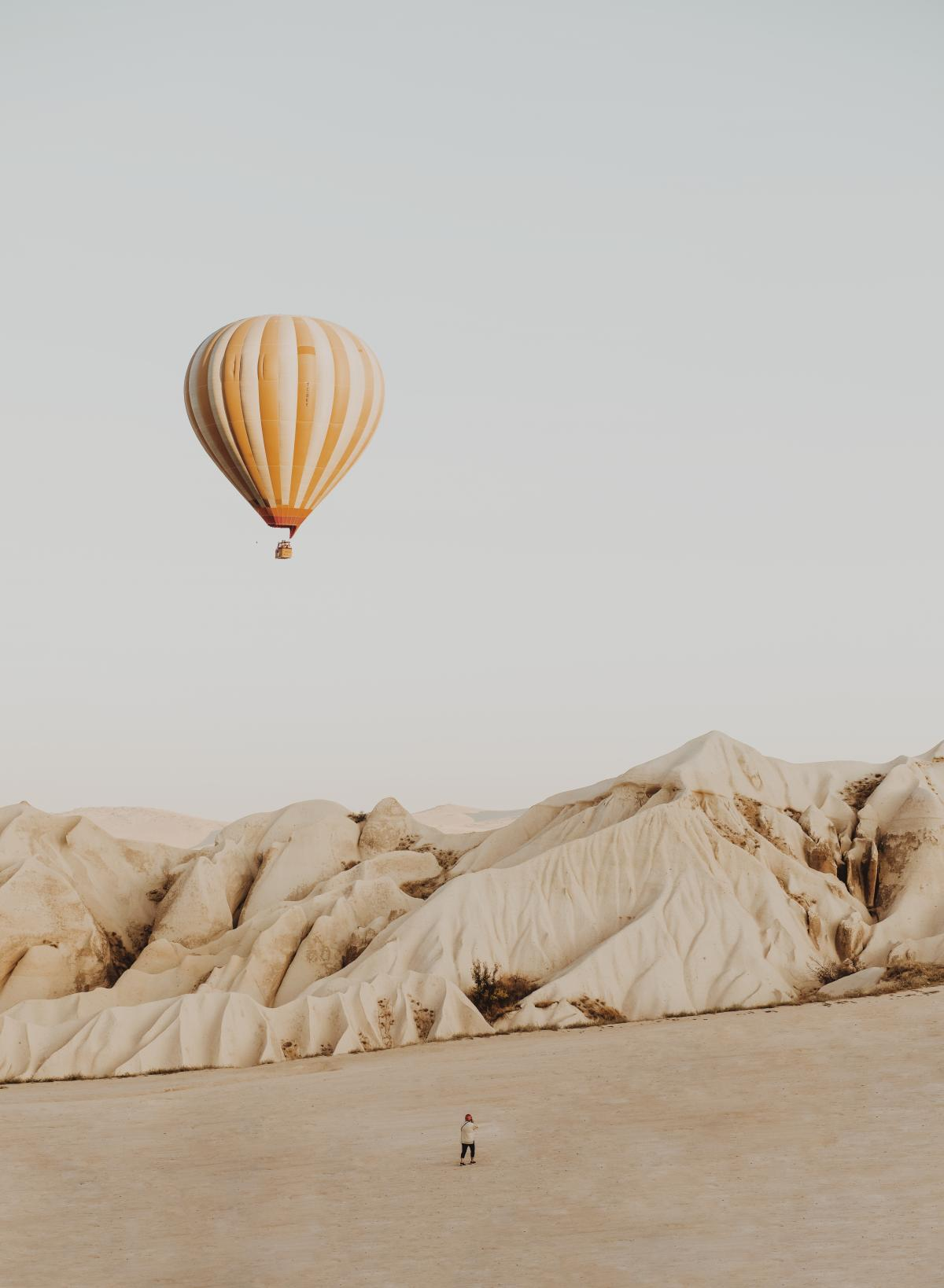 Person Standing on Desert Front of Hot Air Balloon