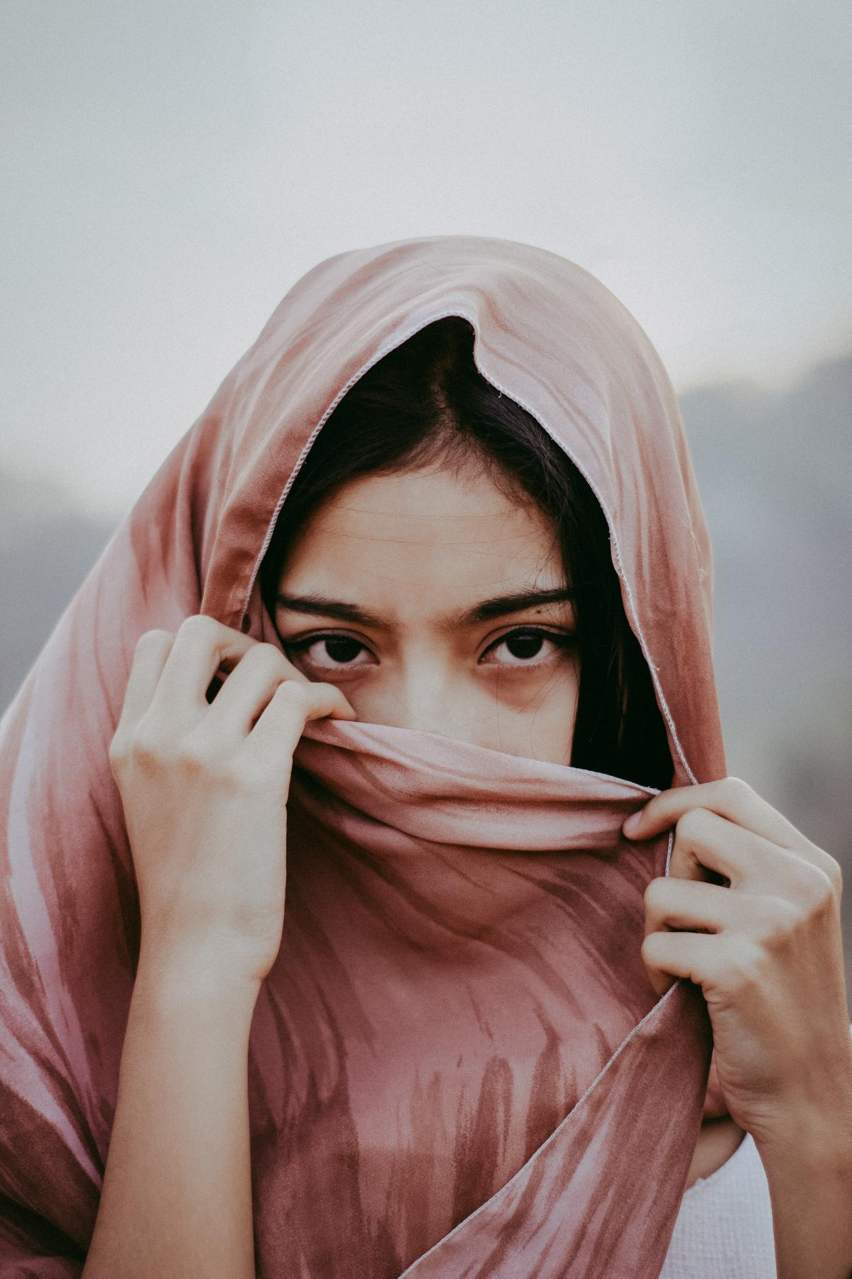 Portrait Photo of Woman Covering Her Mouth with Brown Scarf #424772