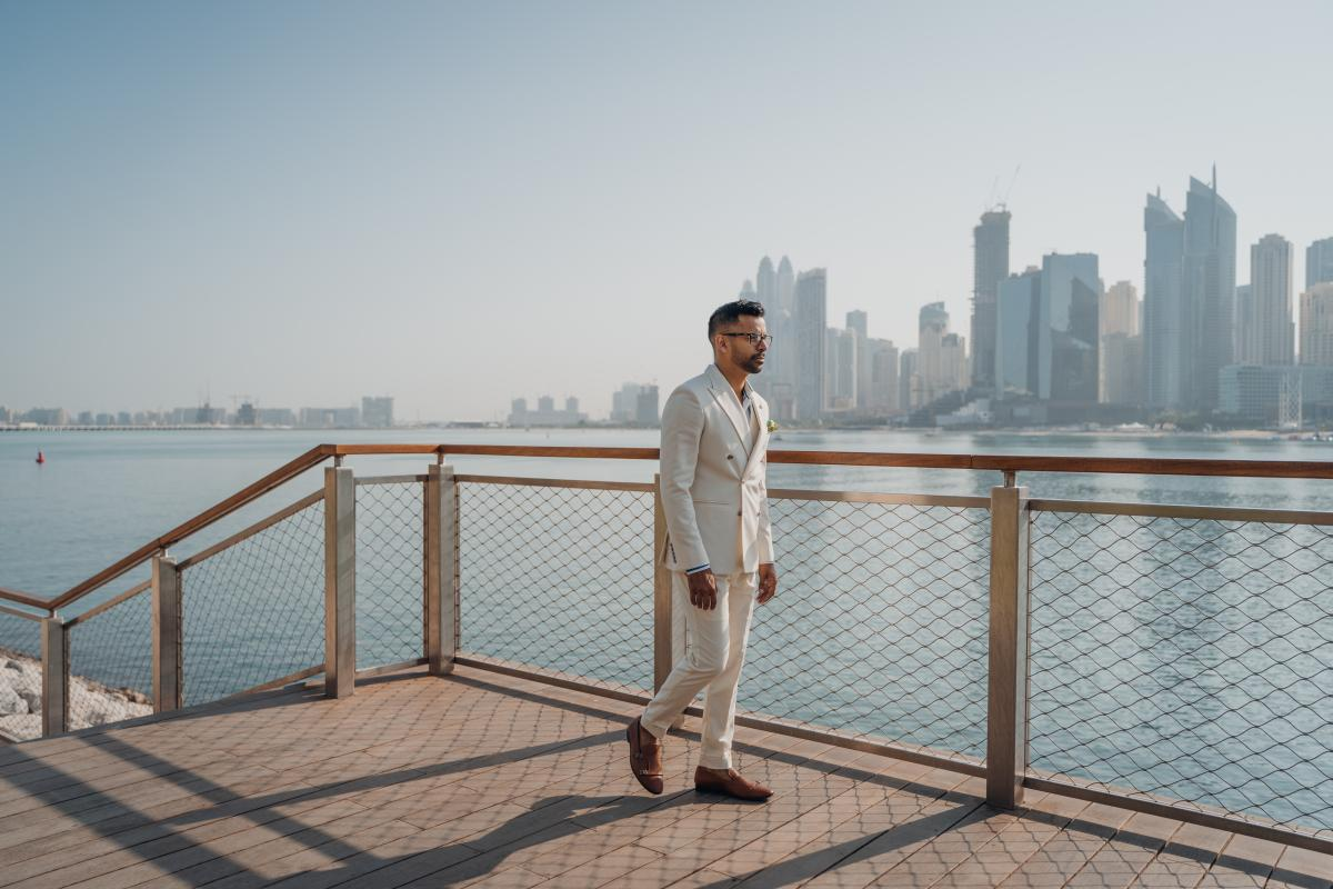 Walking Man Wearing White Suit Beside Fence #426252