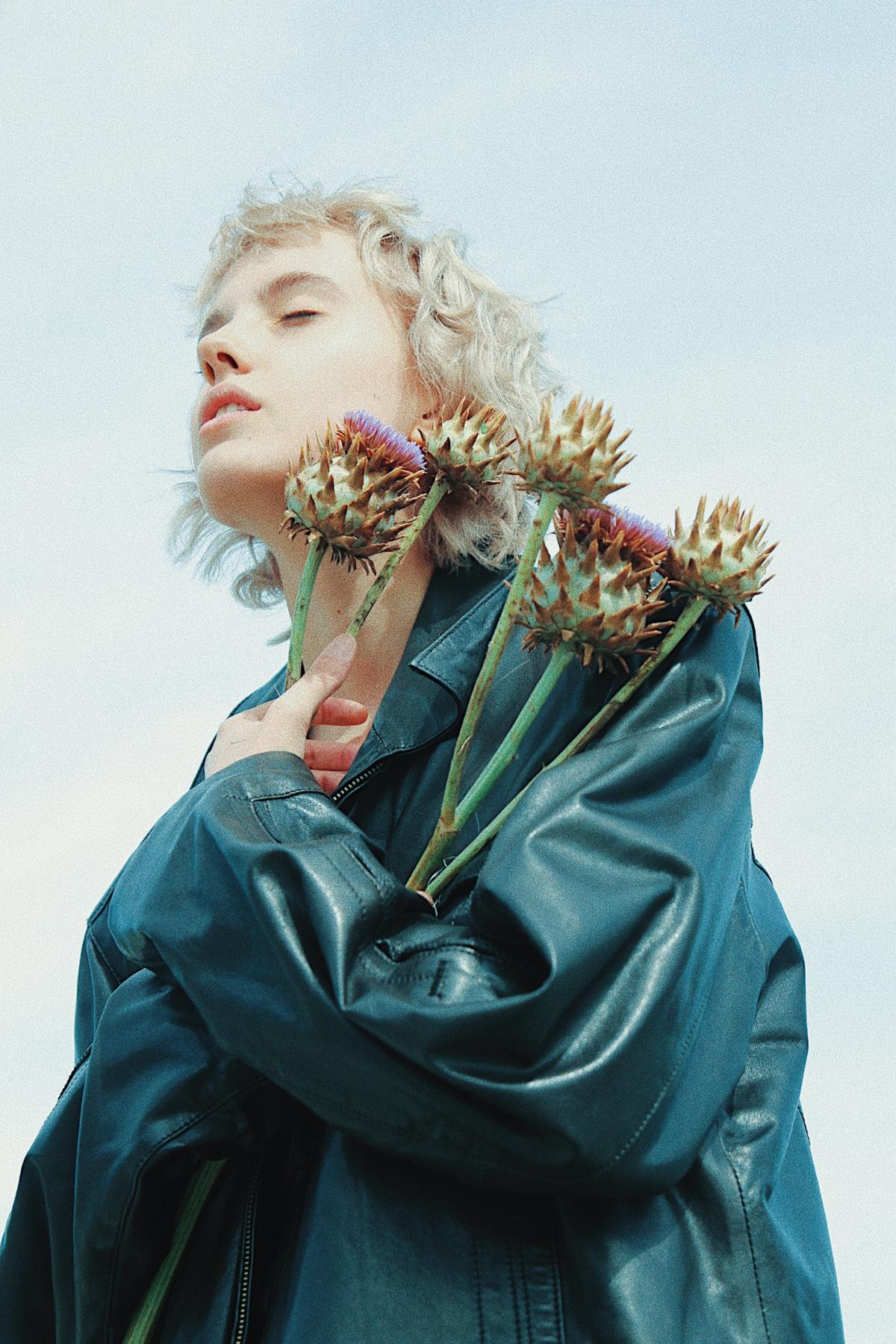 Woman Wearing Green Leather Jacket Holding Flowers