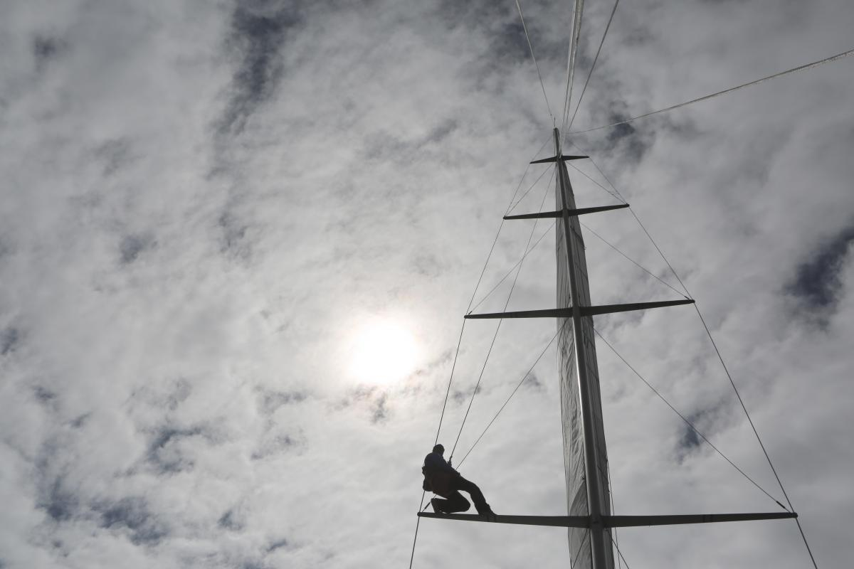 Man Climbing on Top of Structure Under White Clouds during Daytime