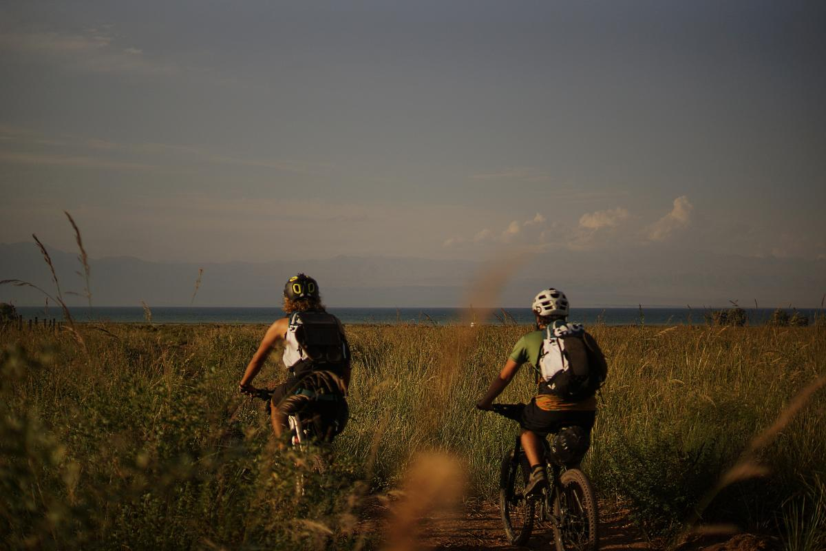 2 People Riding a Bike in the Field