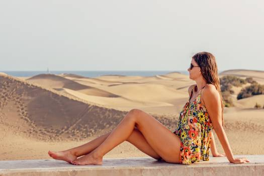 Woman Sitting on Sand at Beach Against Sky #100232