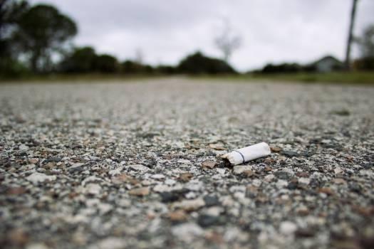 cigarette bud smoking pavement  Free Photo