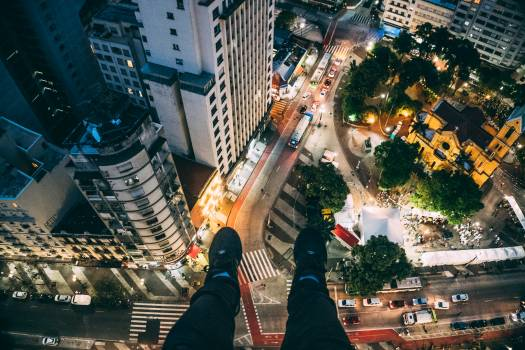 Man Sitting on High Rise Building Taking Photo Below #32072