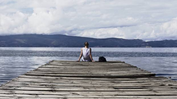 Person Sitting on Brown Wooden Dock Under Cloudy Blue Sky #32135