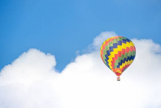 Yellow Blue and Green Hot Air Balloon Flying Near White Clouds Free Photo
