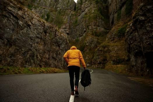 Person Holding Back Pack Walking Black Asphalt Road #32559