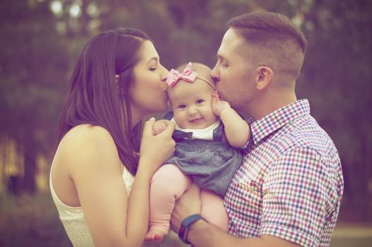Couple Kissing Baby While Carry Free Photo