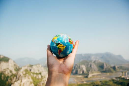 Person Holding World Globe Facing Mountain Free Photo