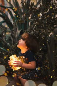 Child Holding Clear Glass Jar With Yellow Light Free Photo