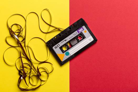 Black Cassette Tape on Top of Red and Yellow Surface #327359